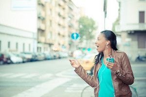 beautiful african young woman listening music earphones in the city