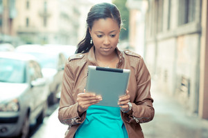 beautiful african young woman using tablet in the city