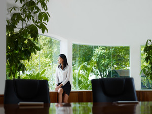 Beautiful Asian female manager looking out of the window in office. Front view, copy space