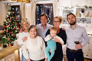 Beautiful big family celebrating Christmat together at home. Illuminated Christmas tree behind them.