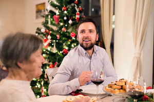 Beautiful big family sitting at the table, celebrating Christmas together at home. Young man with his grandmother. Illuminated Christmas tree behind them.