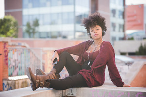 beautiful black curly hair african woman listening music with headphones in town
