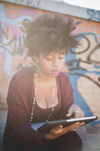 beautiful black curly hair african woman using a tablet in town