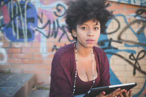 beautiful black curly hair african woman using tablet in town