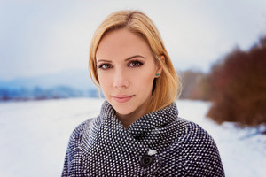 Beautiful blond woman in gray coat in winter nature