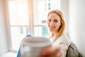 Beautiful blond woman sitting on window sill holding a cup of coffee
