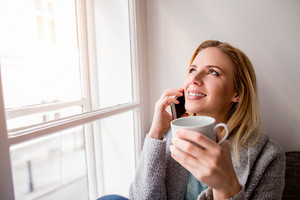 Beautiful blond woman sitting on window sill with smart phone and cup of coffee making a phone call