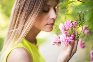 Beautiful blond woman smelling pink rose flowers, close up. Sunny summer.