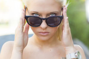 Beautiful blonde girl looking over her sunglasses