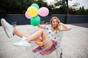 Beautiful blonde girl sitting in shopping cart and holding color balloons outdoors