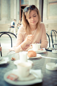 beautiful blonde woman having breakfast at the bar in the city