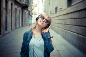 beautiful blonde woman listening to music in the city