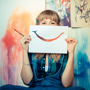 beautiful blonde woman painter smiling in her studio