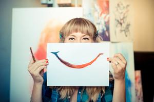 beautiful blonde woman painter smiling in her studio