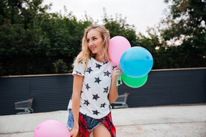 Beautiful blonde woman with colorful balloons in the city