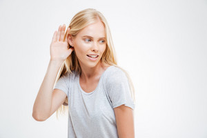 Beautiful blonde woman with hand at the ear to hear better isolated on a white background