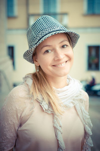 beautiful blonde woman with hat in the city