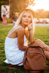 Beautiful blonde young woman in hat with backpack sitting in the park