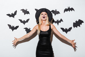 Beautiful blonde young woman in witch costume standing and laughing over white background