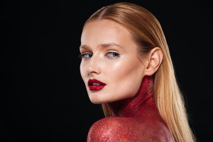 Beautiful body art in red. Close up portrait. Looks back