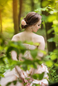 Beautiful bride in pink wedding dress standing green forest