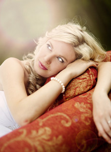 Beautiful bride is lying on the sofa in the forest