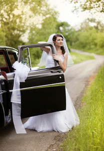 Beautiful Bride with retro car. Outdoor wedding portrait.