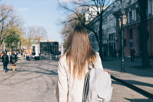 Beautiful brunette girl with long hair in coat goes around town in spring, view from behind