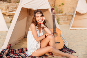 Beautiful brunette hippie girl sitting at the tent and looking at camera