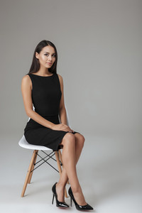 Beautiful brunette woman in black dress sitting on the chair over gray background