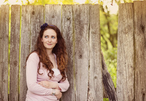 Beautiful brunette woman standing by the old wooden fence
