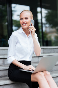 Beautiful business woman talking on mobile phone sitting on the stairs with laptop