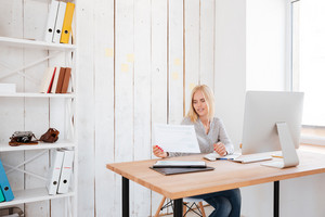 Beautiful business young woman working with papers and computer in office