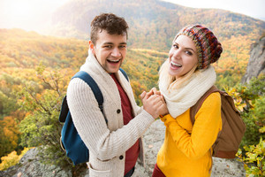 Beautiful couple in autumn nature standing on a rock against colorful autumn forest, holding hands