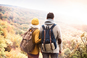 Beautiful couple in autumn nature standing on a rock against colorful autumn forest, rear view