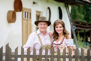 Beautiful couple in traditional bavarian dress standing at the wooden fence in front of an old rural house. Oktoberfest.