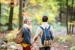 Beautiful couple on a walk in colorful autumn forest. Rear view.