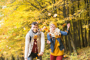 Beautiful couple on a walk in colorful autumn forest throwing leaves up in the air, smiling