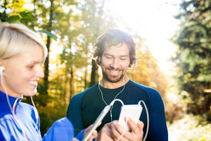 Beautiful couple running together outside in colorful sunny autumn forest using a fitness app on their smartphones. Using phone app for tracking weight loss progress, running goal or summary of their run.