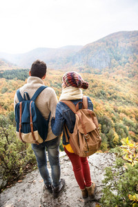 Beautiful couple with backpacks standing on a rock against colorful autumn forest, rear view