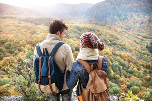 Beautiful couple with backpacks standing on a rock against colorful sunny autumn forest, rear view