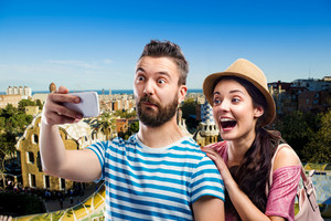 Beautiful couple with smartphone, taking selfie. Sunny summer day in the city.