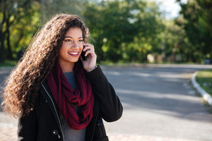 Beautiful dark-skinned young woman dressed in sweater and scarf talking at phone. Against nature background. Look aside.