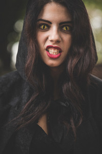 beautiful dark vampire woman with black mantle and hood halloween