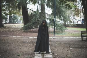 beautiful dark vampire woman with black mantle and hood halloween