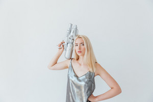 Beautiful fashion blonde girl in silver shiny dress holding water gun isolated on the grey background