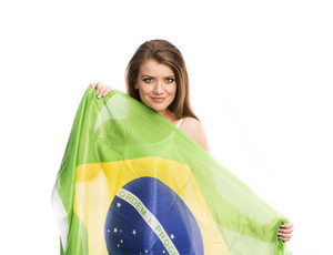Beautiful female sports fan with brazilian flag isolated on white background