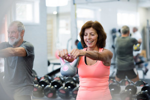 Beautiful fit senior couple in gym working out using kettlebells. Sport, fitness and healthy lifestyle concept.