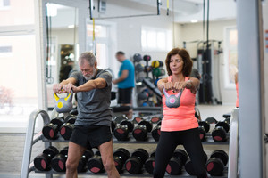 Beautiful fit senior couple in gym working out using kettlebells.