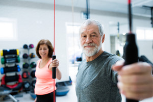 Beautiful fit senior couple in gym working out with vibration bars